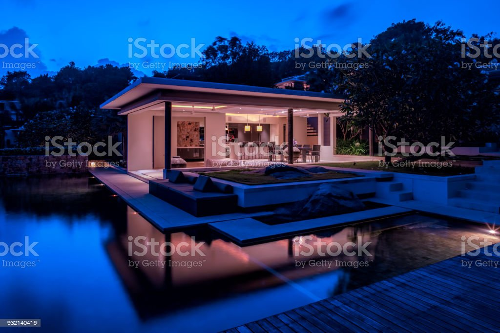 Luxury Home Island Villa At Twilight With Trees And Reflections In Water stock photo