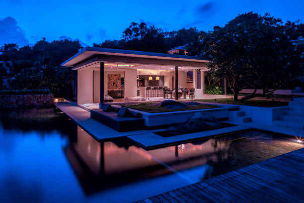 Luxury Home Island Villa At Twilight With Trees And Reflections In Water