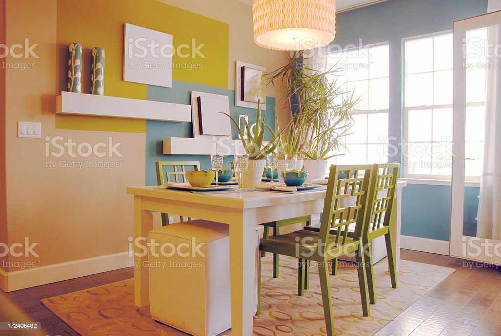 Luxury home with blue and yellow kitchen with green chairs stock photo