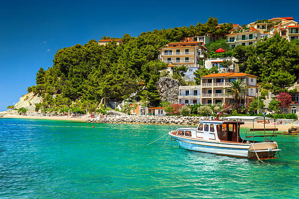 Luxury homes with tourist boat in harbor, Brela, Dalmatia, Croatia stock photo