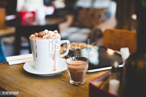 A cup of hot chocolate sits on a table next to a digital laptop. Topped with marshmallows and chocolate balls ready to be drank. A spoon lays on a napkin at the side. A shot glass with extra hot chocolate stands beside the cup as it overflows slightly.