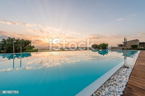 Big and nice luxury swimming pool from an hotel in the sunrise in the morning
