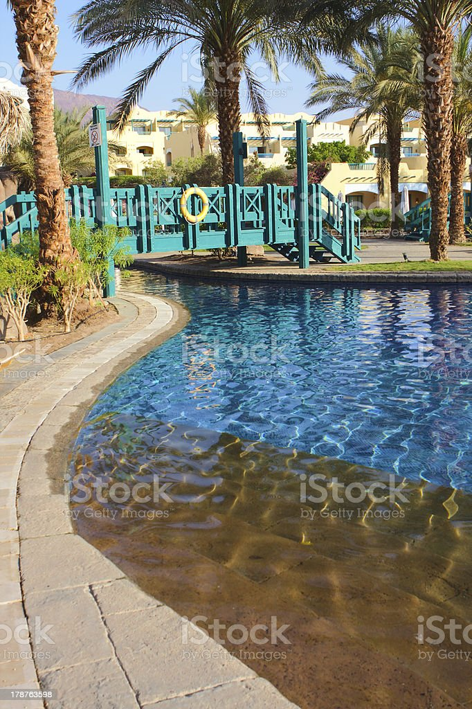 Luxury hotel swimming pool with palm trees and bridge royalty-free stock photo