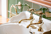 Luxury hotel vintage brass gold plated pillar taps in ensuite bathroom at wash basin