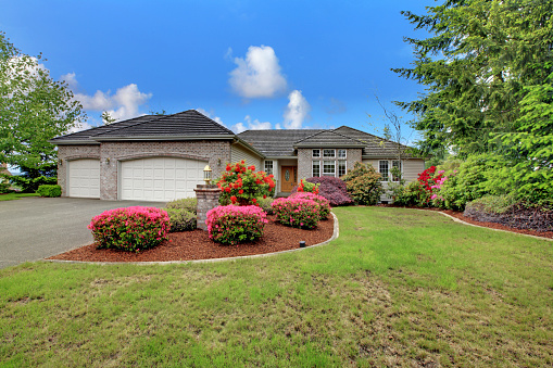 Luxury house exterior with brick trim, tile roof and french windows. Front yard landscape with lawn