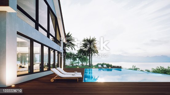 Modern villa exterior with infinity pool and beautiful ocean view at sunset.
