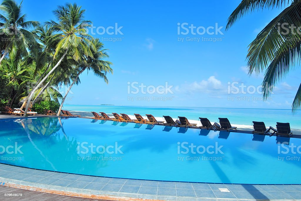 Luxury infinity swimming pool at tropical beach stock photo
