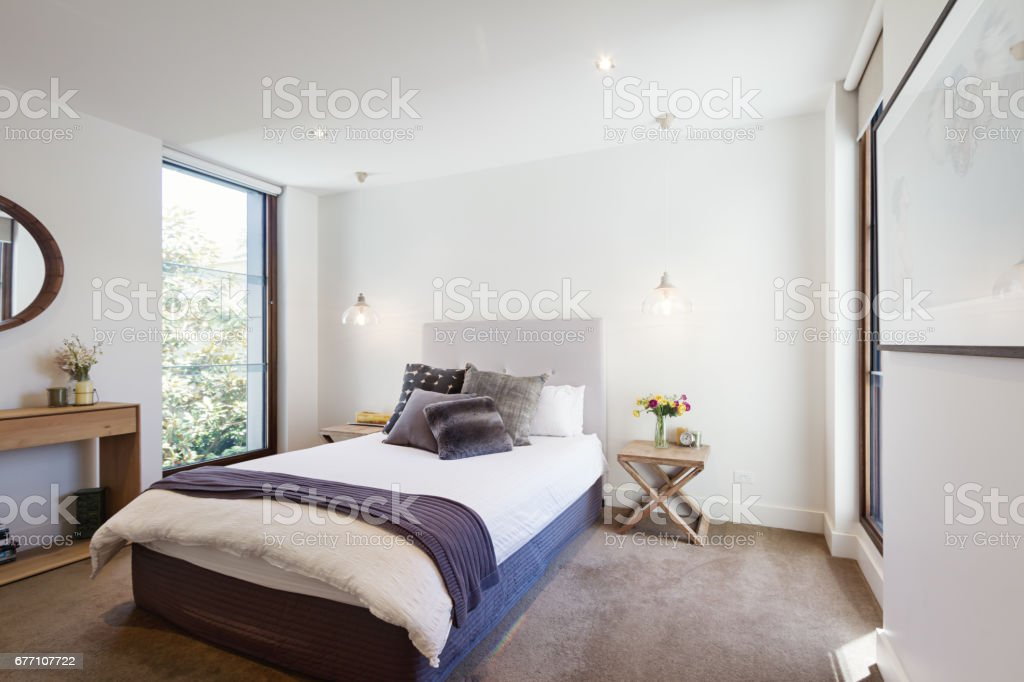 Luxury interior designed bedroom with comfy pillows and throw rug stock photo