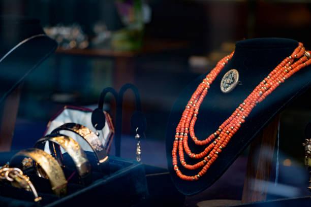 luxuriöses schmuckdisplay mit handgefertigten roten perlenketten und goldarmbändern - canda armband stock-fotos und bilder
