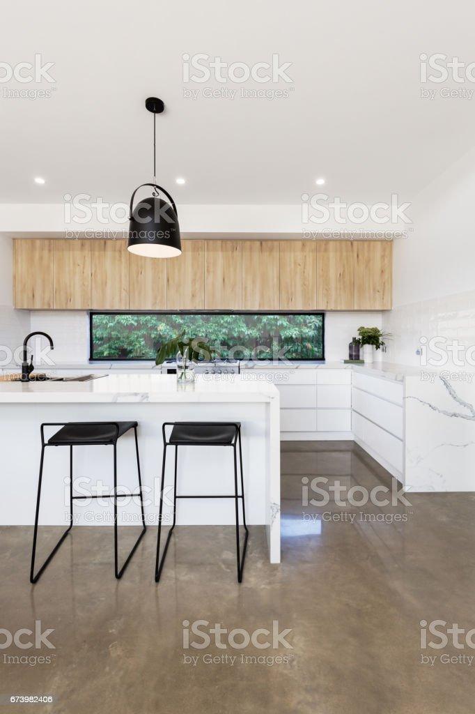 Luxury kitchen with carrera marble waterfall island bench stock photo