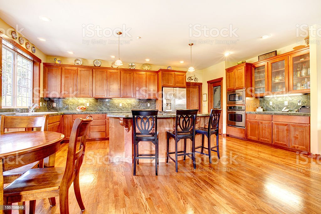Luxury large cherry wood kitchen with green and yellow. royalty-free stock photo