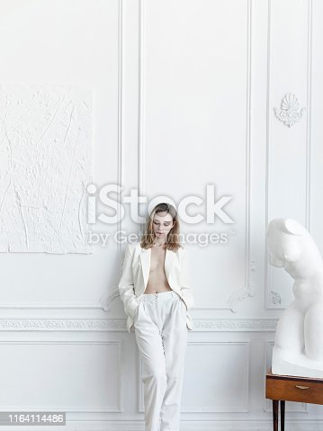 Luxury lifestyle Beautiful young woman wearing white suit: pants and blazer hands in pockets She is Parisian apartment Looks gorgeous confident with fresh natural make-up Amazing vintage style interiour White walls sculpture unique furniture