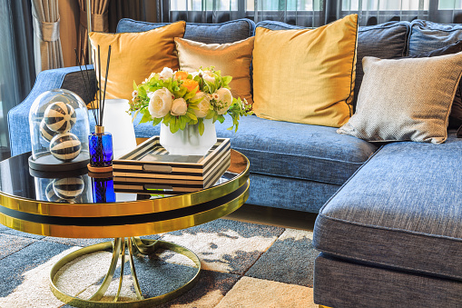A luxury living room with blue sofa and flowers in pot on the table.