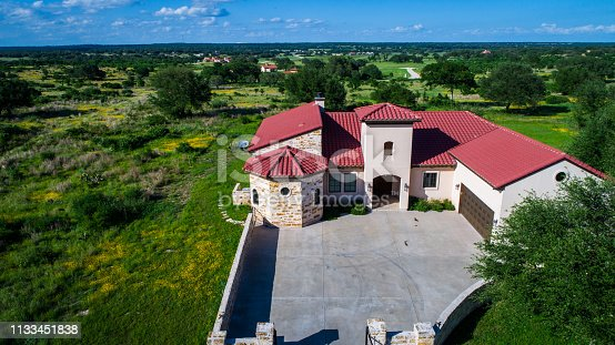 Aerial drone view above green landscape Luxury mansion home on vineyard winery open green Texas hill country landscape with Spanish architecture and large concrete courtyard