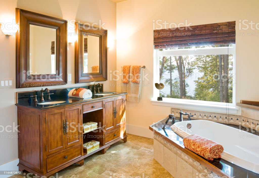 Luxury Master Bath Bathroom With Wood Cabinets Tile Floor And Bathtub Surround Soaking Tub And Twin Sinks With High Quality Fixtures In Traditional Upscale Home Interior Stock Photo Download Image Now