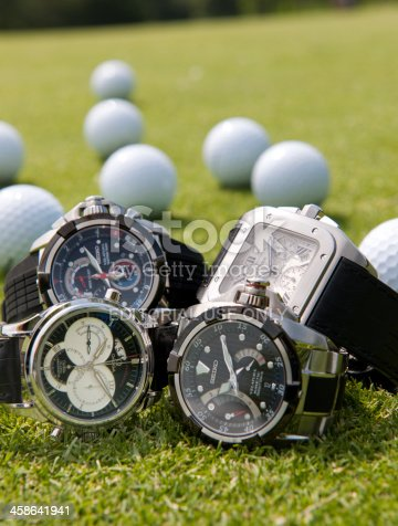Amsterdam, The Netherlands - June 17, 2009: Close up on four luxury wristwatches for men manufactured by Seiko, Omega and Cartier lying on the grass of a putting green on a golf course, golf balls in the background and focus on the foreground. The manufacturers are well known for the production of fashionable, expensive and luxury wristwatches for women and men.