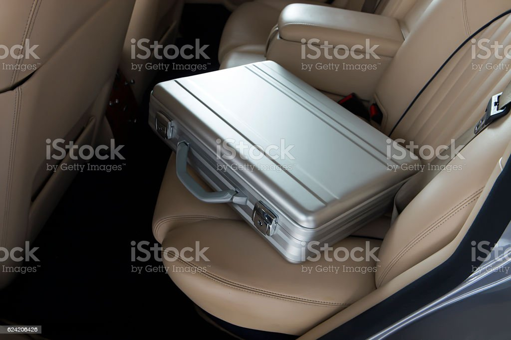 Luxury metal briefcase on a vinage car back seat. stock photo