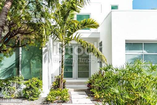 Luxury modern entrance architecture of house in Florida city island on travel, sunny day, property real estate with garden landscaping decoration, green glass windows