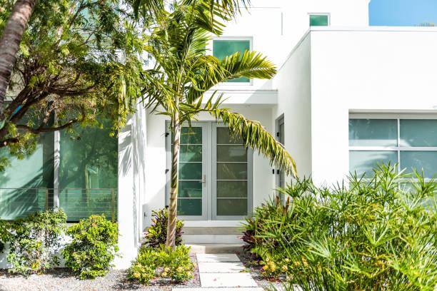 luxuriöse moderne eingangsarchitektur von haus in florida stadtinsel auf reisen, sonniger tag, immobilien mit gartengestaltung dekoration, grüne glasfenster - haus in florida stock-fotos und bilder