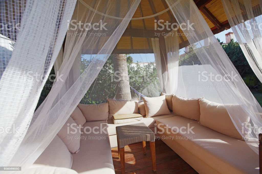 Luxury modern gazebo with soft furniture and curtains inside garden...