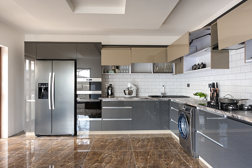 Spacious luxury well designed modern grey, beige and white kitchen with marble tiles floor