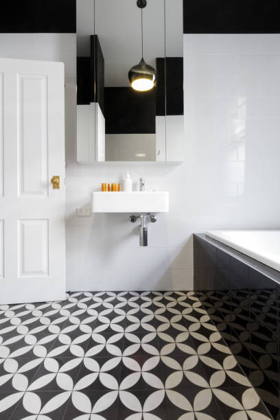 Luxury monochrome designer bathroom renovation with patterned floor tiles stock photo