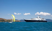 """Small sailing boat sailing past a luxury motor yacht in the Whitsunday Islands, Queensland Australia aa blue sky and sea water for copy space."""