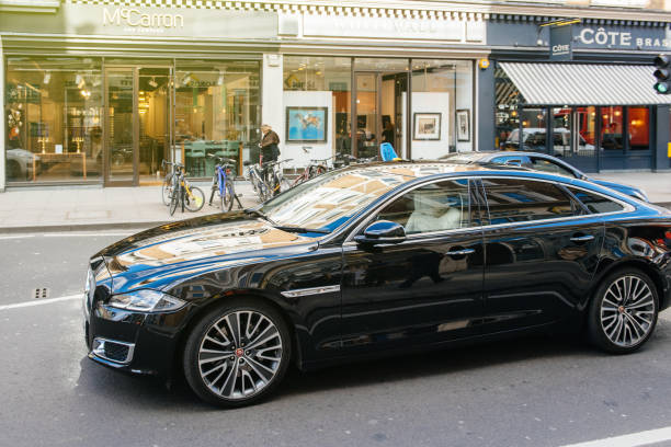 Luxury new black Jaguar XJ AUTOBIOGRAPHY LWB driving London: Luxury new black Jaguar XJ AUTOBIOGRAPHY LWB driving on the crowded london street with open shoppings and commerces in the background. jaguar xj stock pictures, royalty-free photos & images