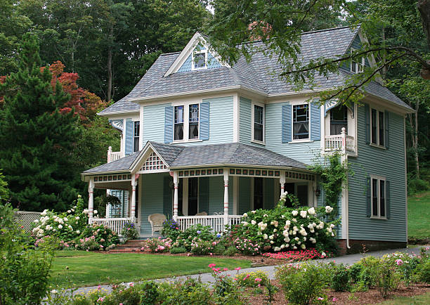 Luxury New England House with Blue Clapboard, Sandwich, Massachusetts, USA. Sandwich, MA, USA - September 9, 2007: Luxury New England Colonial House with Blue Clapboard, Sandwich, Cape Cod, Massachusetts, USA. Front yard, landscaped grass, flowers, trees, house entrance, blue window shutters and chairs on the porch are in the image. colonial style stock pictures, royalty-free photos & images