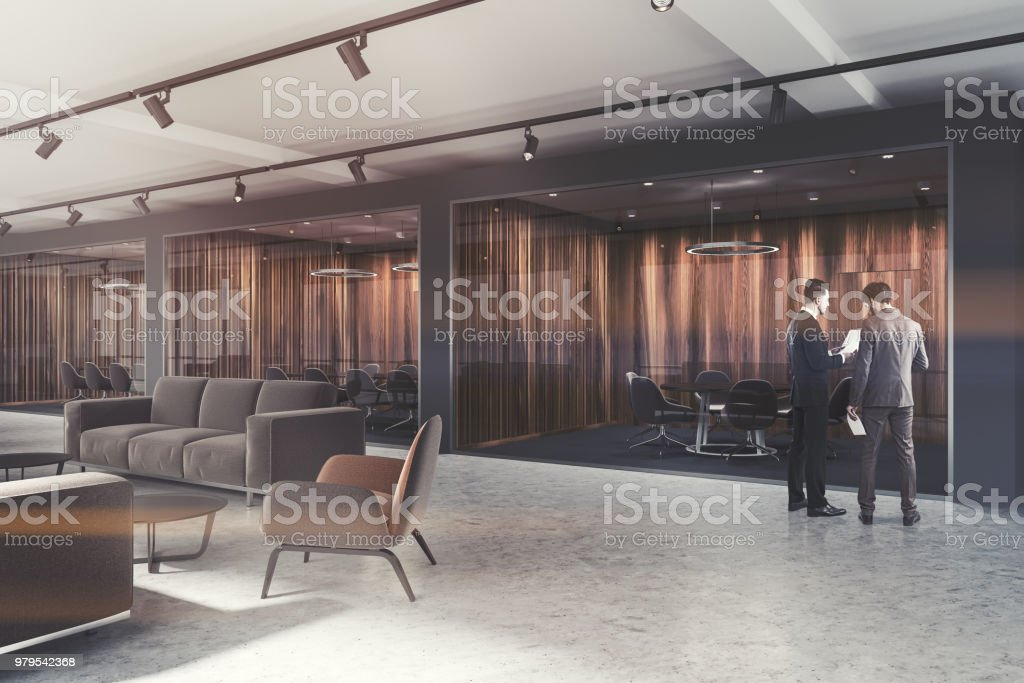 Lobby of a luxury office with dark gray and dark wooden walls, a...