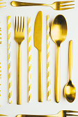 Golden cutlery and party whistlers over a white background