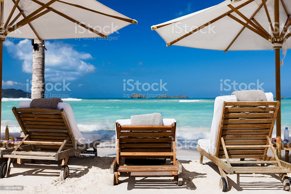Luxury recliner chairs and umbrella on a Caribbean beach royalty-free stock photo