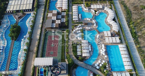 1082419790 istock photo Luxury resort hotel  Swimming Pool with water park aerial view 907615110