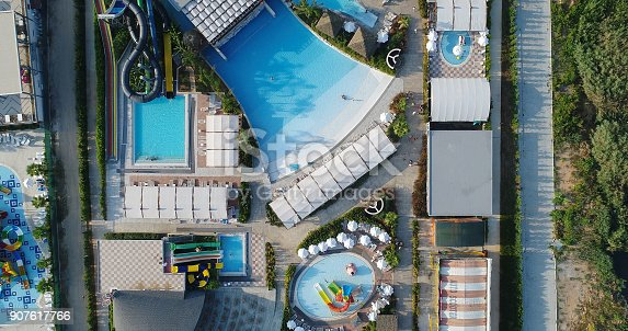 1082419790 istock photo Luxury resort hotel  Swimming Pool with water park aerial view 907617766