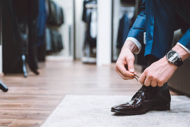 Luxury retail store Man dressed in an elegant business suit is trying on shoes to go with the suit. They must be comfortable and elegant looking at the same time. menswear stock pictures, royalty-free photos & images