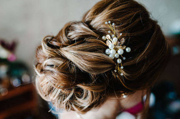 Luxury. Rich Stylish Brunette with Pearly Beads. Elegant Style. Close-up shot of female hair-do made as a strand of hair fixed with a gold hair clip.