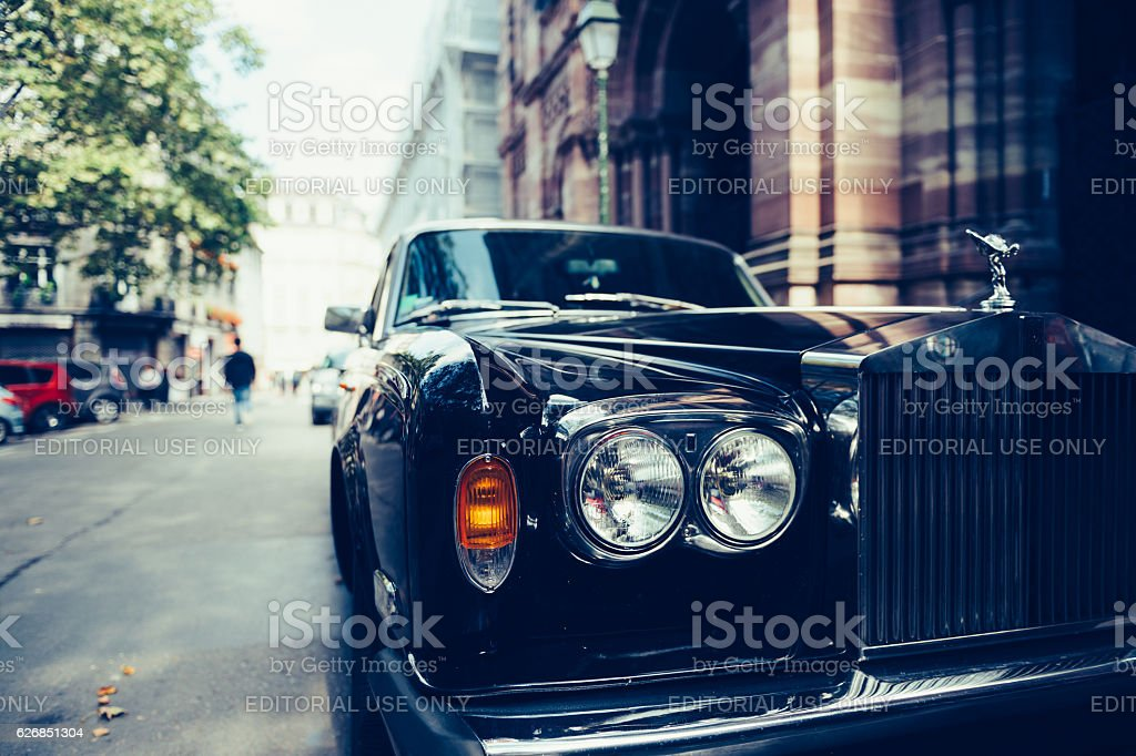 Luxury Rolls Royce car on Paris Street Paris, France - September 12, 2016: Front view of Exclusive Luxury Rolls-Royce car limousine parked in city during fashion wedding vip event waiting for passenger. Rolls-Royce Limited is a British car-manufacturing and, later, aero-engine manufacturing company founded by Charles Stewart Rolls and Sir Frederick Henry Royce on 15 March 1906 as the result of a partnership formed in 1904. Antique Stock Photo