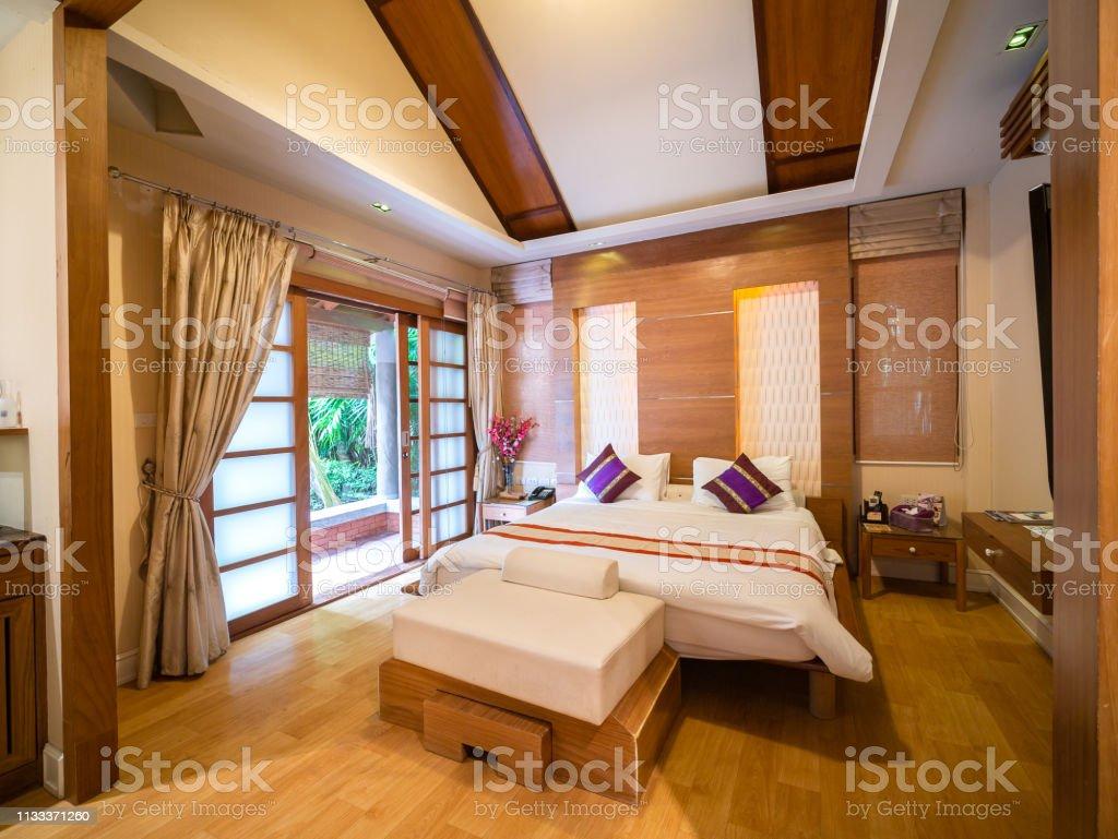 Luxus-Zimmer mit Bett in warmem Licht und Blick auf den Baum, japanischer Stil – Foto