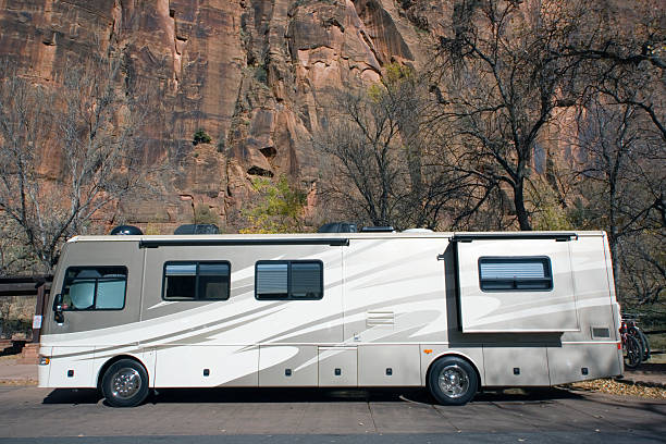 A luxury RV parked in the woods stock photo