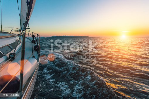 Luxury sailing ship yacht boat in the Aegean Sea during beautiful sunset.