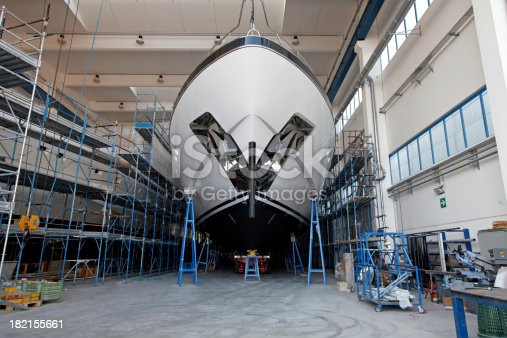 Front view of a large luxury motor yacht in a ship building facility