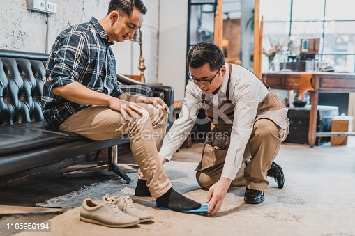 Courteous Taiwanese shoe merchant assisting customer as he tries on a variety of casual and dress shoes.