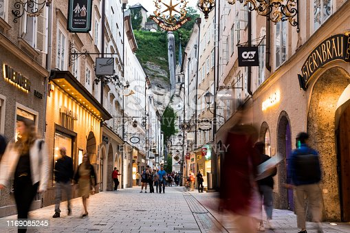 Salzburg, Austria - 7 August, 2019: wide angle color image depicting the old fashioned streets and luxury stores of Salzburg, Austria, illuminated in early evening. Many people and tourists are walking the cobbled streets, exploring the charming atmosphere of this Austrian city.