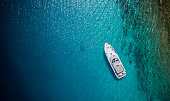Luxury small yacht anchoring in shallow water, aerial view. Active life style, water transportation and marine sport.