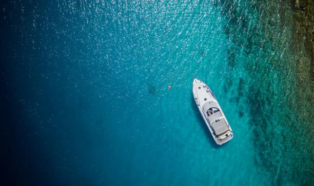 pequeño yate de lujo de anclaje en aguas poco profundas - yacht fotografías e imágenes de stock