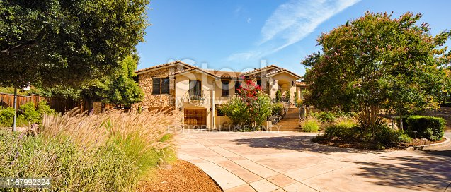 Luxury Spanish styled house and driveway panorama in San Jose California with lush greenery and decorative grass, photographed from the street.