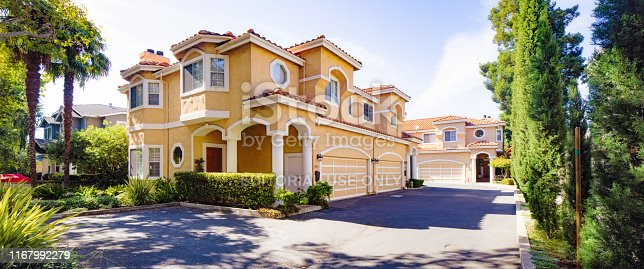 Luxury Spanish styled two storied house and driveway panorama in San Jose California with nicely landscaped greenery, photographed from the street.