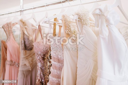 Grate choice of gorgeous fashion dresses hanging on racks in woman's wardrobe. A big variety of sparkling clothes.