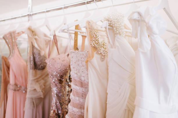 luxus funkelnden damenkleider auf kleiderbügeln - kleid mit verzierung stock-fotos und bilder