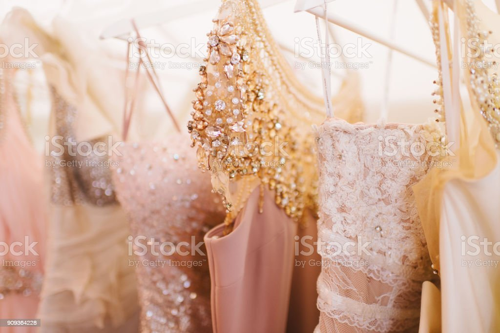 Luxury sparkling women's dresses on hangers stock photo